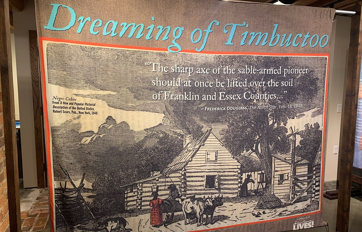Dreaming of Timbuctoo display panel showing a woodcut of a homesteader's cabin